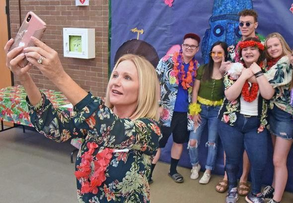 First Lady Kathryn Burgum, wearing a multicolored Hawaiian shirt, poses for a selfie with five Bismarck Century High School students in the background