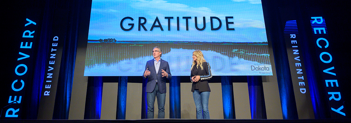 Governor Doug Burgum and First Lady Kathryn Burgum speaking on stage with the word