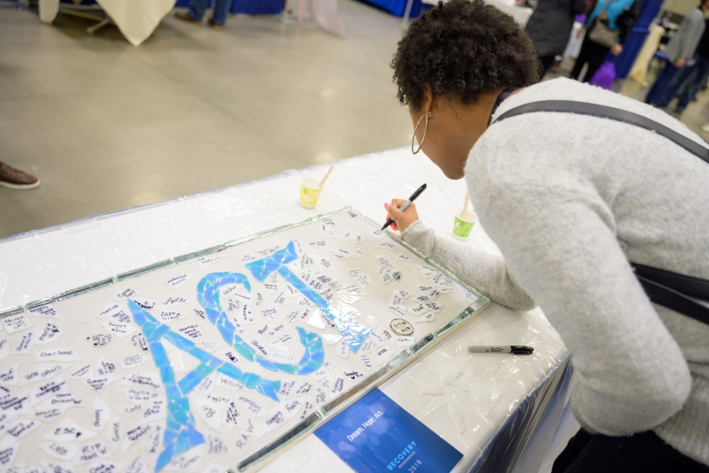 """Woman signing a white mosaic with the word """"Act"""" in blue tiles"""